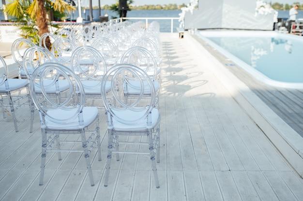 Le sedie di vetro stanno in fila in una bellissima cerimonia di matrimonio.