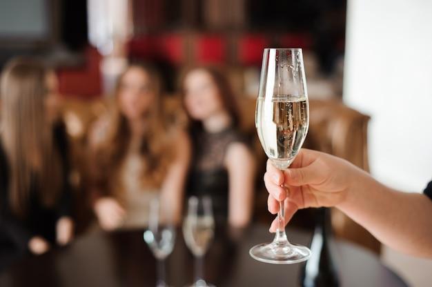 Bicchiere di champagne sullo sfondo di amici a una festa