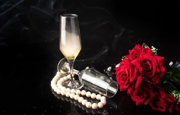 Bicchiere di champagne, rose rosse, collana di perle su sfondo nero, fuoco selettivo.