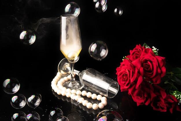 Bicchiere di champagne, rose rosse, collana di perle e bolle di sapone, sfondo nero, fuoco selettivo.