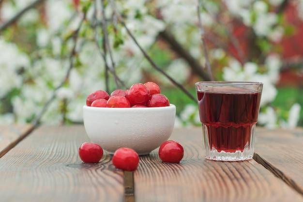 Un bicchiere di liquore alla ciliegia e una ciotola di frutti di bosco congelati di un albero in fiore. alcool fatto in casa a base di bacche di ciliegia.
