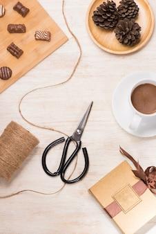 Bicchiere di latte al cioccolato e cioccolatini vari sul tavolo con confezione regalo