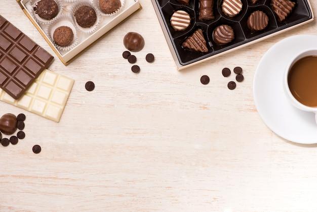 Bicchiere di latte al cioccolato e cioccolatini di varietà sul tavolo