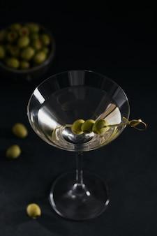 Bicchiere di classico cocktail martini secco con olive sul tavolo di pietra scura su uno sfondo nero.