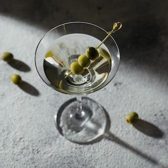 Bicchiere di cocktail martini secco classico con olive su uno sfondo di pietra grigia
