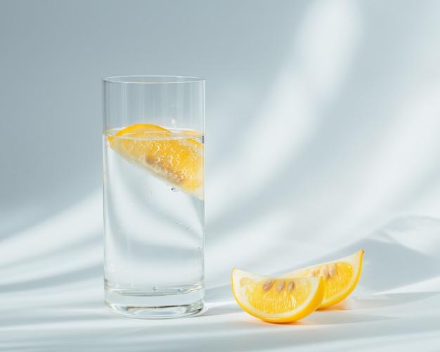Bicchiere di acqua frizzante minerale pulita con ghiaccio e limone su uno sfondo bianco con il sole. luce con ombre dure e riflessi dal vetro. colazione, bevanda fresca del mattino