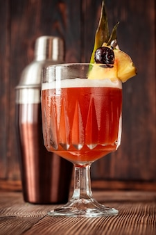 Bicchiere di club cocktail guarnito con spicchio di ananas e ciliegia al maraschino