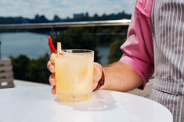 Bicchiere di cocktail. bell'uomo elegante che indossa la camicia rosa normale che tiene un bicchiere di cocktail freddo
