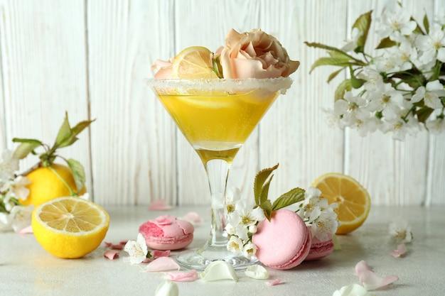 Bicchiere di cocktail, ingredienti e fiori su sfondo di legno
