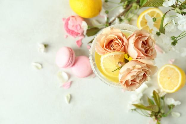 Bicchiere di cocktail, ingredienti e fiori sul tavolo strutturato bianco