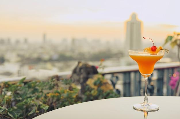 Bicchiere di cocktail sul tavolo con vista di paesaggio urbano di edifici grattacielo di bangkok in background, thailandia