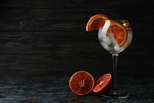 Bicchiere di cocktail con pompelmo sul tavolo smokey nero