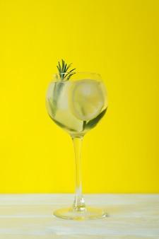 Bicchiere di cocktail con limone e rosmarino su sfondo giallo