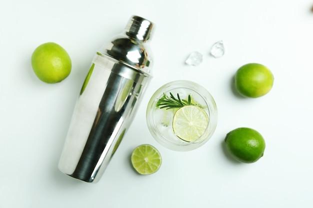 Bicchiere di cocktail con calce e ingredienti sulla superficie bianca