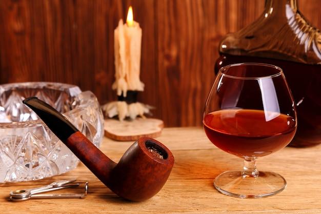 Un bicchiere di cognac e una pipa sul tavolo di quercia