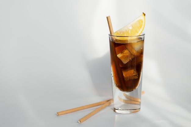 Bicchiere di cola con ghiaccio, limone e paglia su uno sfondo bianco