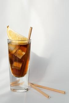 Bicchiere di cola con ghiaccio, limone e paglia su un muro bianco