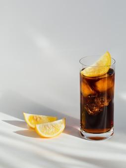 Bicchiere di cola con ghiaccio e limone sulla superficie bianca
