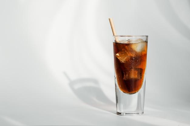 Bicchiere di cola con ghiaccio e paglia su una superficie bianca