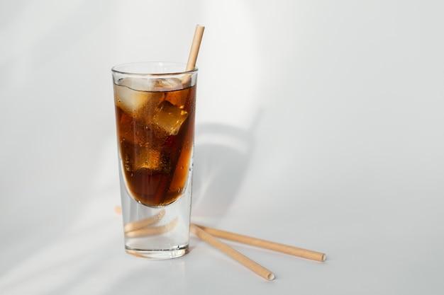 Bicchiere di cola con ghiaccio e paglia su una parete bianca