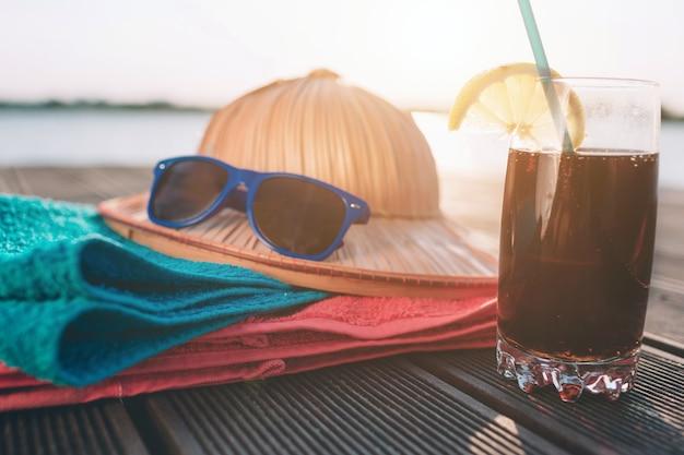 Bicchiere di cola sul molo in legno