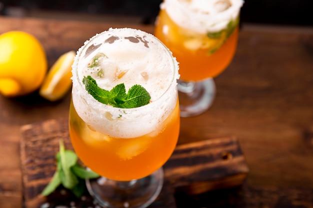 Un bicchiere di birra fredda con limone e menta, bevanda tradizionale latinoamericana michelada sul tavolo vicino, foto con soft focus.