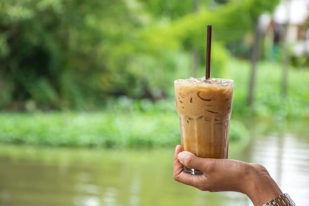 Bicchiere di caffè espresso freddo in mano sfondo sfocato vista albero e acqua.