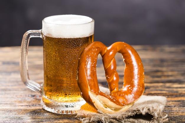 Bicchiere di birra chiara fredda con un pretzel su un tavolo in legno rustico.