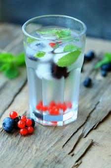 Bicchiere di bevanda estiva rinfrescante fredda con frutti di bosco e cubetti di ghiaccio sul tavolo da vicino