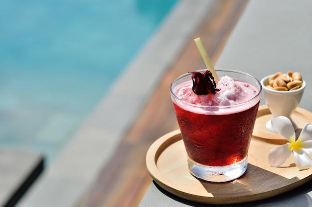 Bicchiere di succo di roselle freddo sul bordo di una piscina