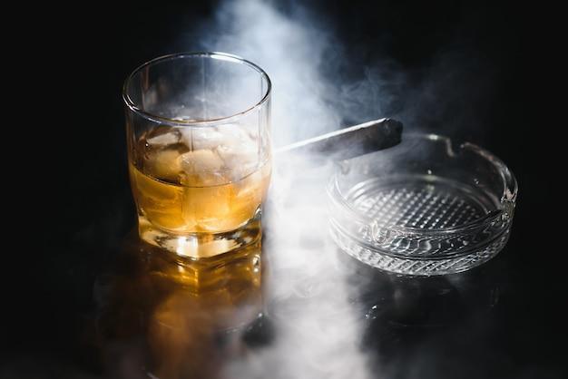 Bicchiere di whisky freddo con sigaro sul nero