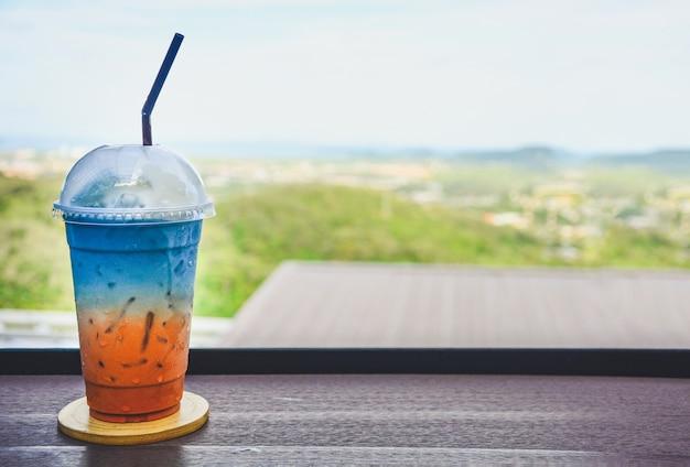 Bicchiere di tè al latte tailandese ghiacciato colorato mescolato con succo di pisello di farfalla su un tavolo di legno