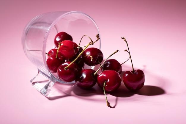 Contenitore di vetro adagiato su uno sfondo rosa con ciliegie che ne escono