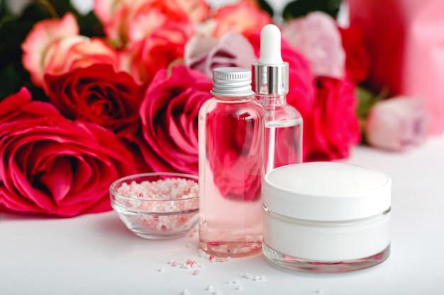 Bottiglie per la cosmetica in vetro crema siero sapone olio sul tavolo bianco fiore floreale rose rosa rosse prodotto di bellezza biologico naturale spa cura della pelle bagno trattamento corpo set di cosmetici con rosa