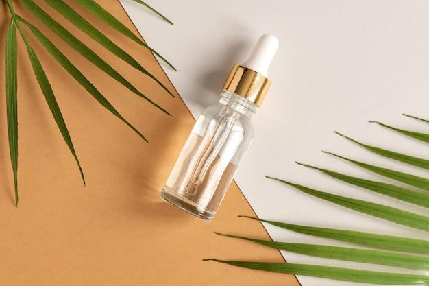Flaconi per la cosmetica in vetro con contagocce su fondo beige con foglie tropicali.