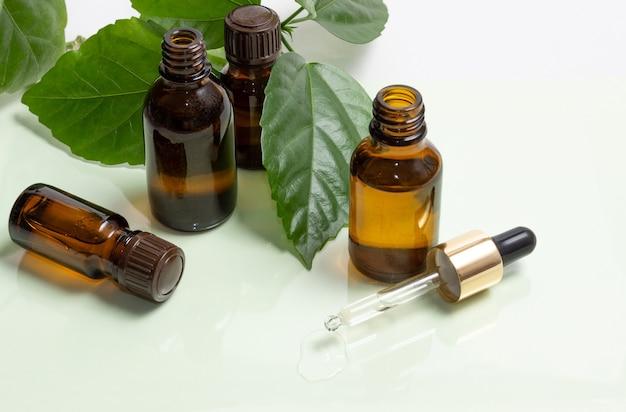 Flaconi per la cosmetica in vetro con un contagocce accanto a foglie verdi su sfondo bianco