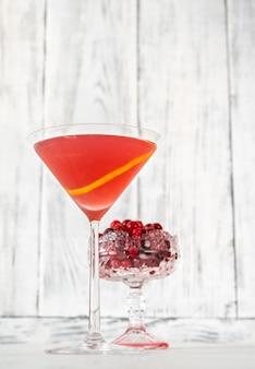 Bicchiere di cocktail cosmopolita con mirtilli rossi freschi