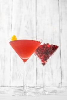 Bicchiere di cocktail cosmopolita con un bicchiere di mirtilli rossi freschi