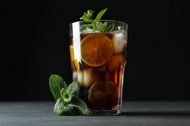 Bicchiere di cuba libre e menta contro la superficie scura