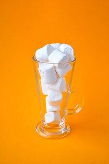 Bottiglia di vetro con marshmallow su sfondo giallo. concetto creativo. copia spazio. cannuccia