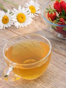 Tazza di vetro di tè verde, fiori di camomilla, ciotola di vetro con fragole fresche sui bordi di legno. vista dall'alto.