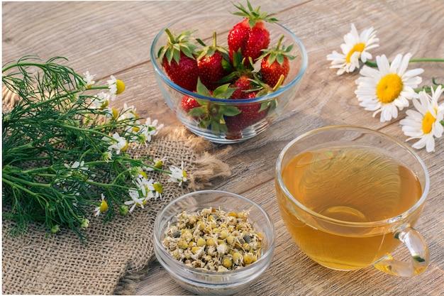 Tazza di vetro di tè verde, fiori di camomilla, ciotole di vetro con fiori secchi di matricaria chamomilla e fragole fresche sulle tavole di legno. vista dall'alto.