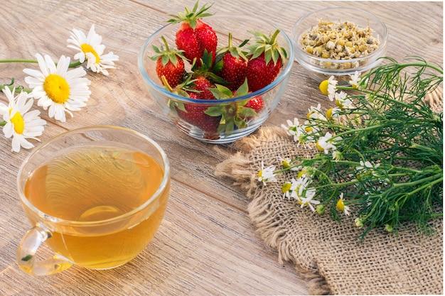 Tazza di vetro di tè verde, fiori di camomilla, ciotole di vetro con fiori secchi di matricaria chamomilla e fragole fresche sulle tavole di legno.