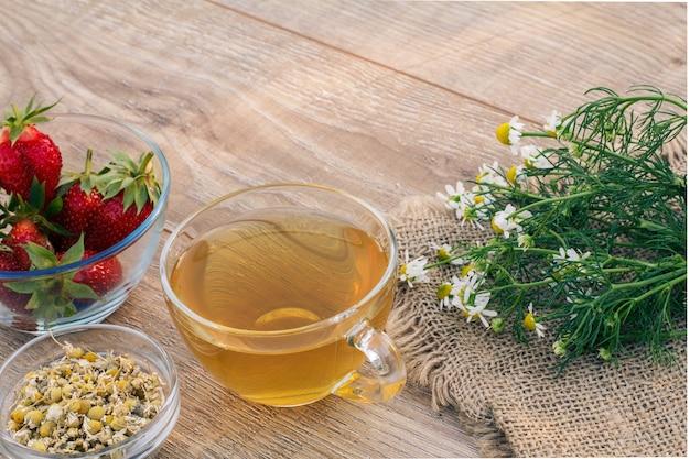 Tazza di vetro di tè verde, fiori di camomilla su tela di sacco, ciotole di vetro con fiori secchi di matricaria chamomilla e fragole fresche sulle tavole di legno.