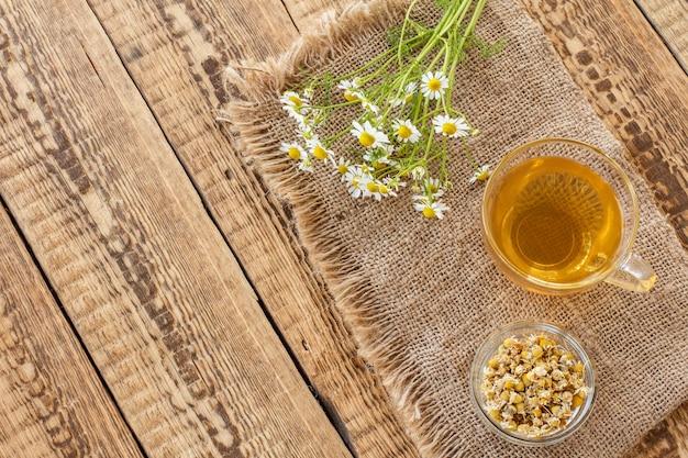 Tazza di vetro di tè verde, piccola ciotola di vetro con fiori secchi di matricaria chamomilla e fiori di camomilla bianca fresca su tela di sacco su fondo di legno. vista dall'alto.