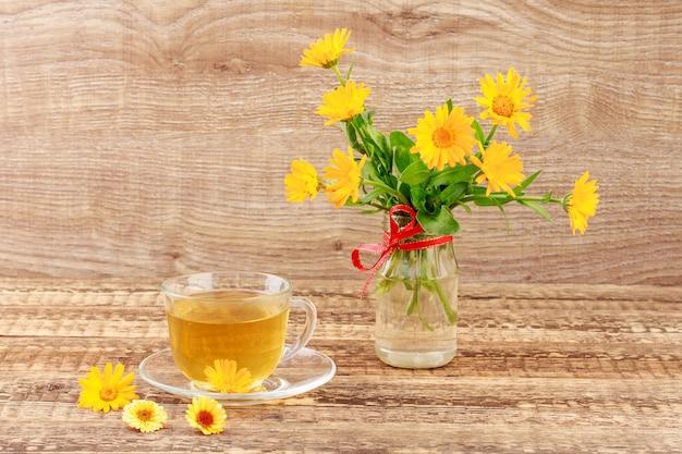 Tazza di vetro di tè verde con fiori di calendula e bouquet fresco di calendula arancione in vaso. sfondo di tavole di legno. bevanda salutare.