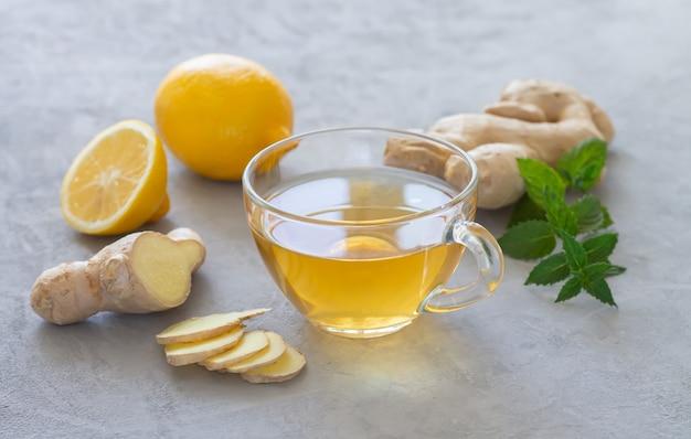 Tazza di vetro di tè allo zenzero caldo sano con menta e limone