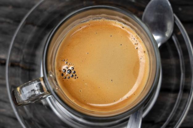 Tazza di vetro di caffè espresso caldo su tavola di legno, primo piano, vista dall'alto