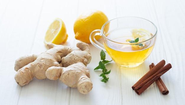 Tazza di vetro di tè caldo con zenzero, limone, menta e cannella su un tavolo di legno bianco