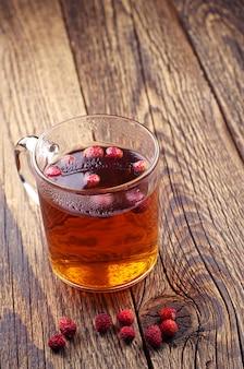 Tazza di vetro di tè caldo con fragoline di bosco su un tavolo di legno vintage